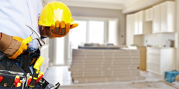 Close em cinto de ferramentas, martelo e capacete amarelo numa reforma